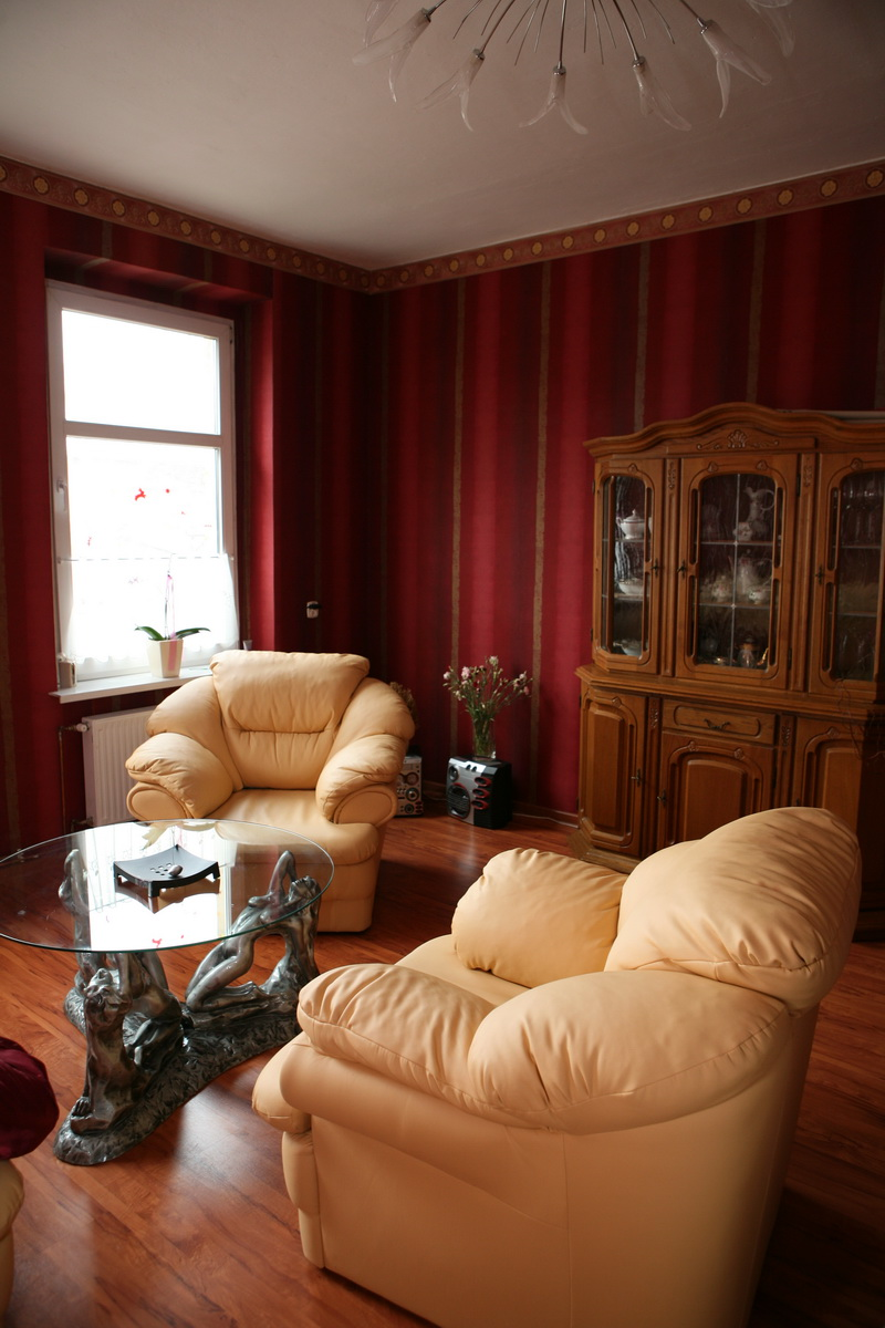 Exotic-living-room-with-red-wallpaper-and-glass-top-table-cream-armchair-and-wood-floor-with-chandelier